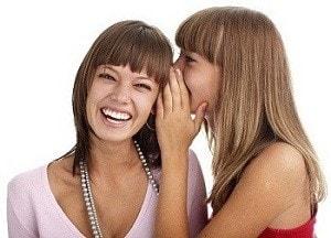 Chicas hablando al oido riendo