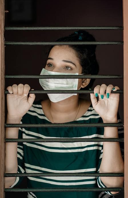 Mujer con mascarilla en ventana con rejas. No te contagies emocionalmente