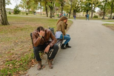 Pareja pensativa sentada en cada punta de un banco. Una relación de pareja tóxica