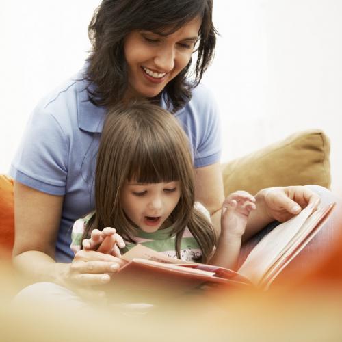 Madre que da apoyo en estudios a su hija con un libro