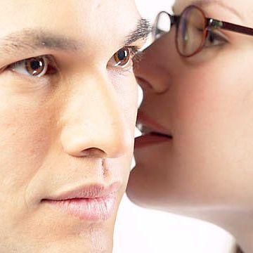 Mujer hablándole al oido a su pareja, representando la comunicación en la pareja