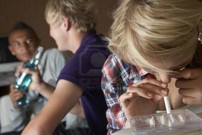 Muchachos bebiendo de fondo mientras otro se droga