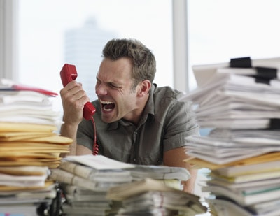 Hombre sufriendo estrés laboral, gritándole al auricular del teléfono