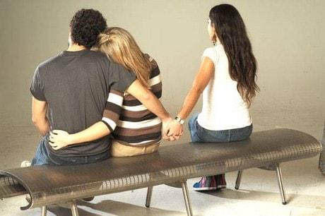 Pareja abrazada mientras el da la mano a otra mujer. Infidelidad.