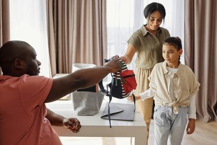 Padre entrega mochila a su hija mientras nueva pareja observa