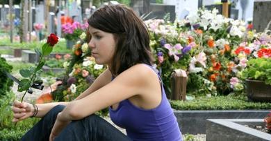 Chica sentada en el cementerio llorando la muerte de un ser querido