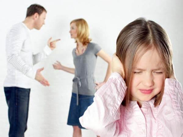 Niña tapándose los oidos . Discusión de padres atrás. Ruptura y familia