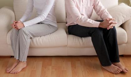 Pareja sentada separada en sofá. Superar ruptura