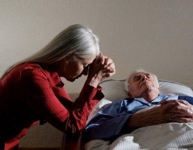 Mujer llorando junto a enfermo terminal en la cama