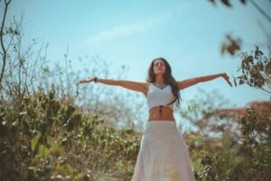 Chica de pié en la naturaleza con brazos extendidos