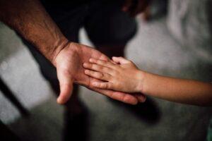 Mano de adulto extendida y encima mano de un niño representando la bondad y generosidad paternal