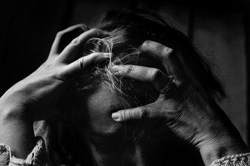 Mujer apretandose la cabeza con los dedos por el estrés